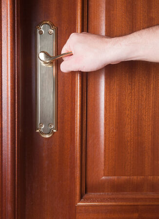 Hand gripping the handle of a door inside home