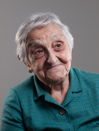 Elderly woman with positive expression in a studio shot and isolated on grey background