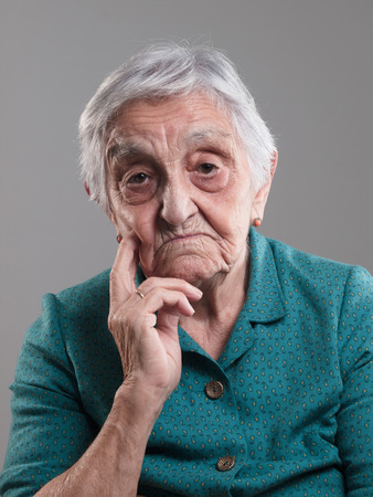 80 90: Elderly woman portrait in a studio shot. Old woman had her hand on chin and sad Stock Photo