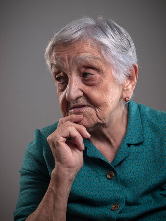 85 90: Elderly woman portrait in a studio shot. Old woman had her hand on chin and is looking aside.