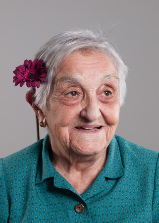 85 90: Elderly woman similing with a flower in her ear in a studio shot.