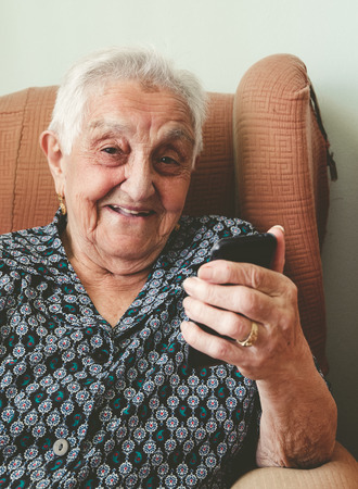 Elderly woman smiling with a smartphone in her hand. Elderly woman is happy. Stock Photo