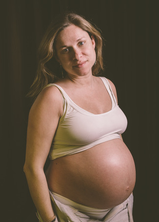 30 35 years: Pregnant woman looking at camera in a studio portrait