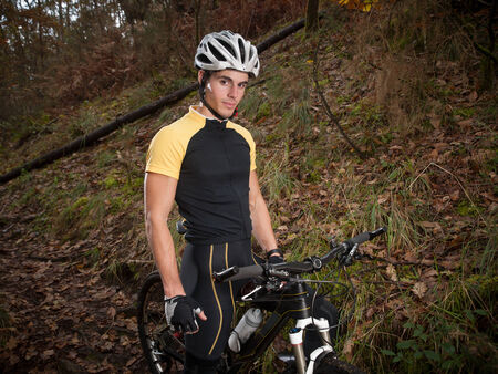 btt: Cyclist in the forest standing and looking at camera.