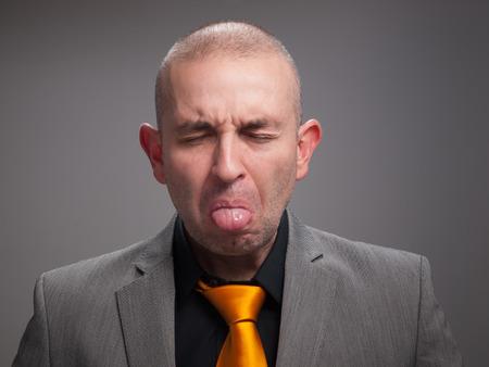 ojos cerrados: Hombre de negocios que fuera su lengua con los ojos cerrados.