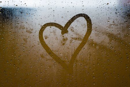 Heart painted in the crystal of a window in a rainy day