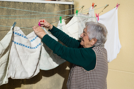 adult 80s: Elderly woman hanging out the washing on the terrace of his house Stock Photo