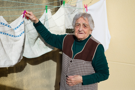 Elderly woman hanging out the washing on the terrace of his house. Woman is looking at camera. photo