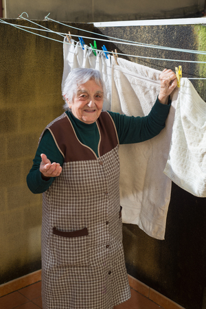 Elderly woman hanging out the washing on the terrace of her house. Woman is smiling. photo