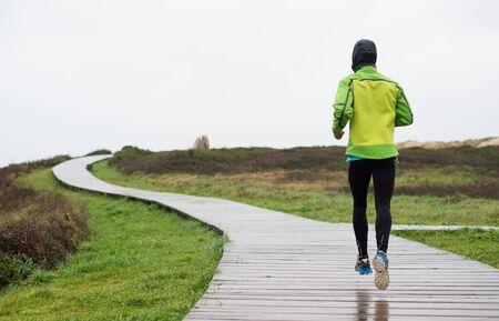 UOMO pioggia: Runner uomo che corre in un giorno di pioggia. L'uomo � in esecuzione su una passerella Archivio Fotografico