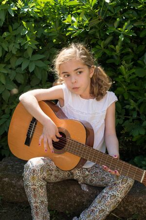 spanish guitar: Seven years old girl playing a spanish guitar outdoors Stock Photo