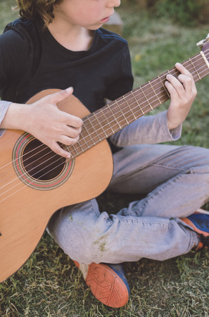 spanish guitar: Little blond boy playing spanish guitar outdoors. The childs identity is hidden.