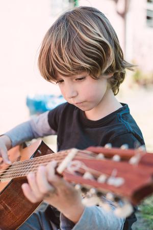 spanish guitar: Blond little boy playing spanish guitar outdoors