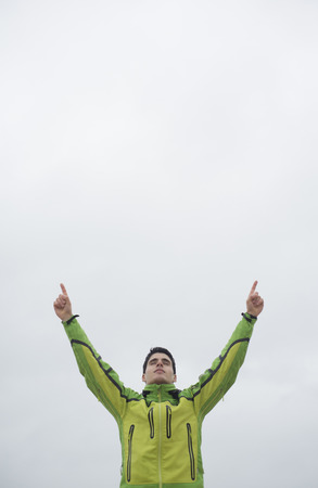 victory symbol: Runner man with arms raised in victory symbol against cloudy sky
