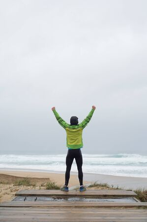 victory symbol: Runner man on the shore of the beach with hands up in victory symbol in a rainy day Stock Photo