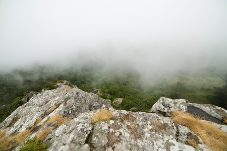 edge of cliff: At the edge of a cliff in the mountains with fog Stock Photo