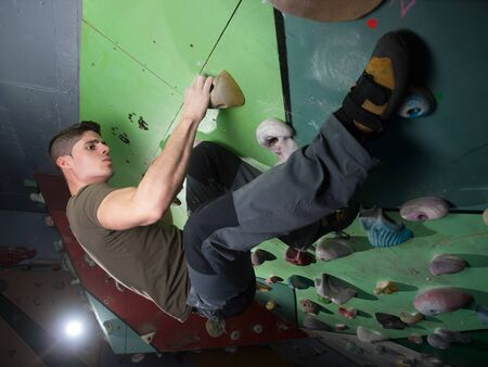 young man climbing wall rock indoors