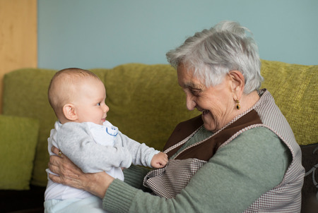 the great grandmother: Elderly woman with a beautiful baby at home. The baby and the lady are laughing at each other.