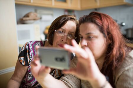 teaching adult: Mature woman learning to use a smartphone under the watchful gaze of her daughter in law Stock Photo