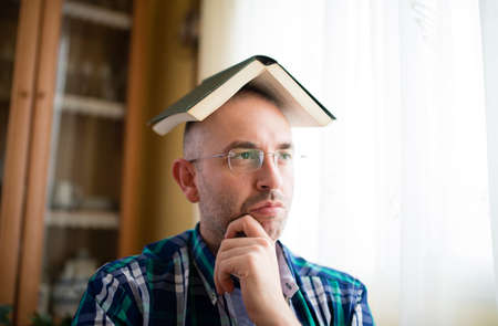 Adult man with a book on his head. He is thoughtfully photo