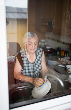 80s adult: Elderly woman washing dishes in the kitchen Stock Photo