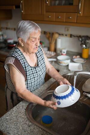 lavar trastes: Platos de edad avanzada que se lavan en la cocina
