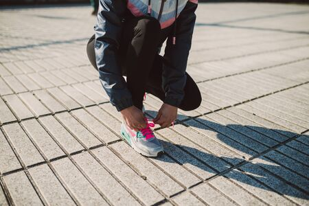 female jogger: Female jogger tying her running shoes preparing for a jog outdoors Stock Photo
