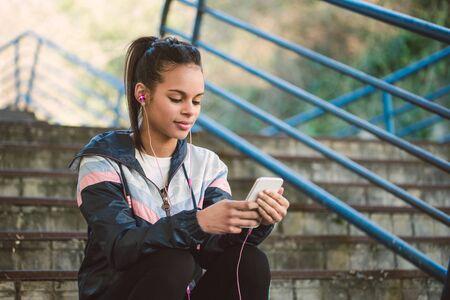 personas escuchando: Hermosa mujer hispana escuchar música después de que se ejecuta en una escalera