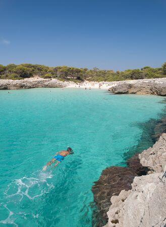 Snorkeling in a beautiful cala in Minorca, cala Talaier, Balearic islands, Spain. photo