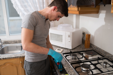 hobs: Man installing a gas hob in a kitchen.