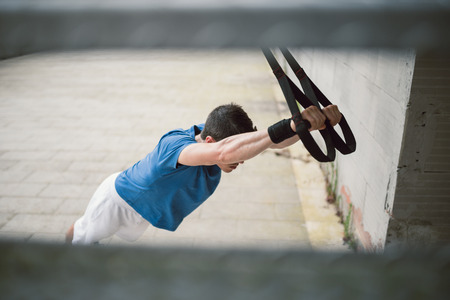 anonymous people: Sporty male exercising with fitness trx straps in the street