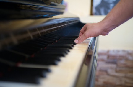 Man playing piano with one hand at home, photo