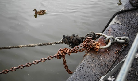Rusty chain tied to an iron ring on the wharf Banque d'images