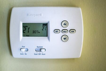 A honeywell thermostat for home central heating fixed to a wall Stock Photo