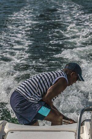 Varadero, Cuba, Jan 2013 - Skipper at work at the rear of catamaran followed by the wave track left behind