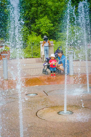 Water fountains in activity as mother and child watch