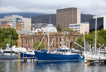 ホバート (タスマニア州) の背後にあるダウンタウンの建物とマリーナ ボートの眺め。