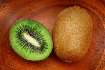 national fruit of china: Cut ripe kiwi fruit on a wooden plate
