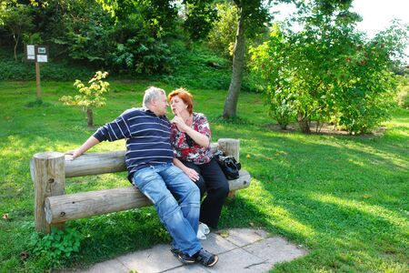 Happy elderly couple talking in the park  photo