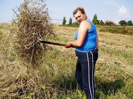 Woman removes hay on a sunny day