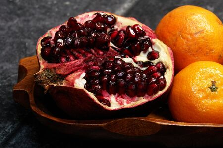 Pomegranate and mandarins on the wooden plate                                 Stock Photo