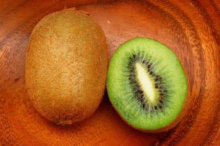 national fruit of china: Kiwi fruit on a wooden plate.
