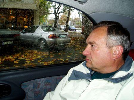 An elderly man looks into the car window
