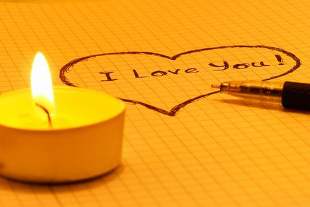 Inscription I Love You on a sheet of notebook with candles                         photo