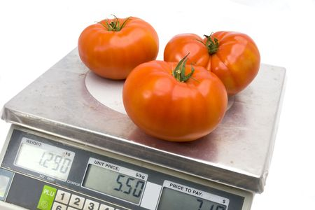 Fresh tomato on the scales that show the weight