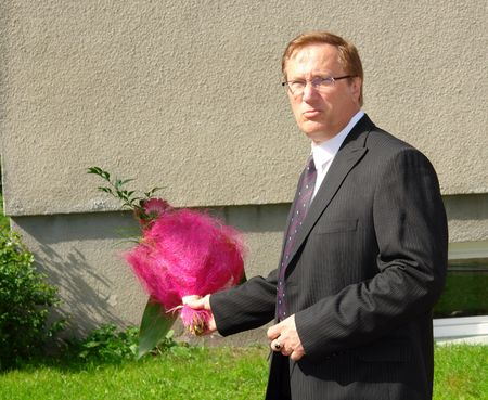 Portrait mature businessman with a bouquet of flowers near the office  Stock Photo - 7342428