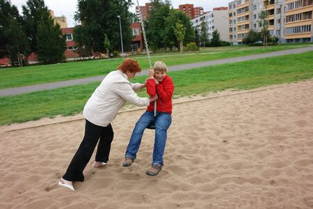 Mother helping his son play  on the playground                                 photo