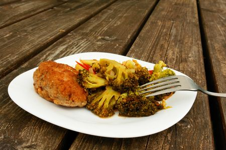 Cutlet and Broccoli in a white plate on wooden table                               photo