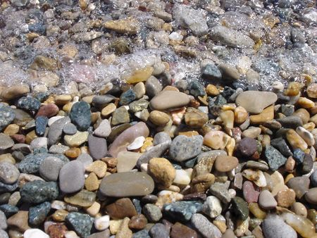 Grey and brown pebbles with stones are in the sea water                                photo