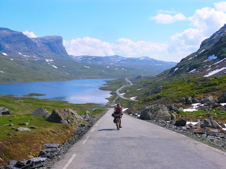 Male mountain bike cyclist riding uphill along a country road; clear summer day                              photo